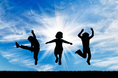 Silhouette happy children jumping. Concept of happiness. Silhouette happy children jumping against the beautiful sky Stock Image
