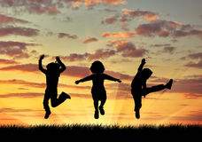 Silhouette happy children jumping. Concept of happiness. Silhouette happy children jumping at sunset Royalty Free Stock Images