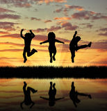 Silhouette happy children jumping. ?oncept of happiness. Silhouette happy children jumping at sunset and reflection in water Stock Image