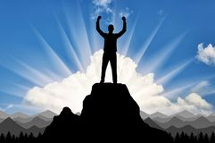Silhouette of a happy climber on top of a mountain which he conquered stock photography