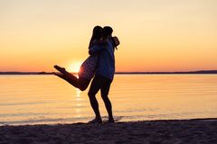 Silhouette of happy couple on beach at sunset, man taking the girl in his arms. Silhouette of happy couple on beach at sunset, men taking the girl in his arms Stock Image