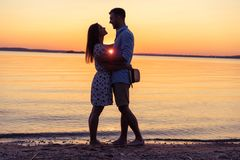 Silhouette of happy couple on beach at sunset, man taking the girl in his arms. Silhouette of happy couple on beach at sunset, men taking the girl in his arms Stock Photography