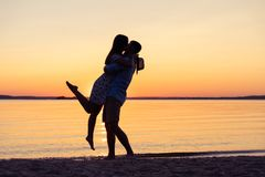 Silhouette of happy couple on beach at sunset, man taking the girl in his arms. Silhouette of happy couple on beach at sunset, men taking the girl in his arms Stock Photos
