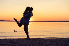 Silhouette of happy couple on beach at sunset, man taking the girl in his arms. Silhouette of happy couple on beach at sunset, men taking the girl in his arms Royalty Free Stock Images