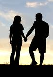 Silhouette of Happy Couple Holding Hands on Walk at Sunset Stock Photo