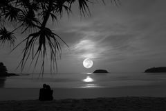 Silhouette of happy couple at luxury fullmoonset . Stock Image