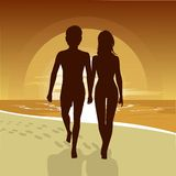 Silhouette of happy couple walking along beach at sunset Stock Photography