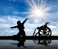 Silhouette happy disabled. Concept of disability and positive. Silhouette happy disabled on a sky background and reflected in water Royalty Free Stock Photos