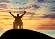 Silhouette happy disabled person. Concept of disability and disease. Silhouette happy disabled person in a wheelchair and sea sunset Stock Photos