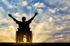 Silhouette happy disabled person. Concept of disability and disease. Silhouette happy disabled person in a wheelchair at sunset Royalty Free Stock Photography