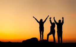 Silhouette of a happy family with arms raised up against beautiful sky. Summer Sunset Stock Image