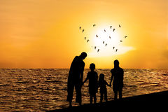 Silhouette of happy family on beach 1 Stock Photos