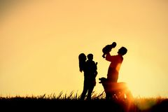 Silhouette of Happy Family and Dog. A silhouette of a happy family of four people, mother, father, baby, and child, and their dog in front of a sunsetting sky Royalty Free Stock Photo
