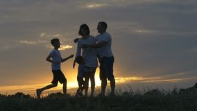 Silhouette of happy family father of mother and two sons playing outdoors in field at sunset. Slow-motion shooting stock footage