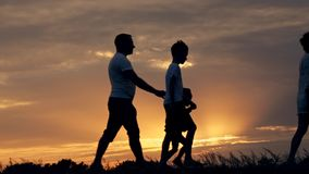 Silhouette of happy family father of mother and two sons playing outdoors in field at sunset. Slow-motion shooting stock video footage