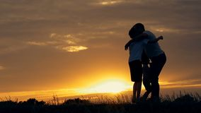 Silhouette of happy family father of mother and two sons playing outdoors in field at sunset. Slow-motion shooting stock video