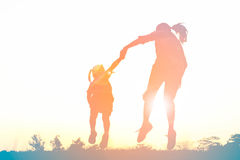 Silhouette of happy family jumping together on the park Stock Photo