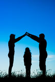 Silhouette of a happy family making the home sign Royalty Free Stock Photo