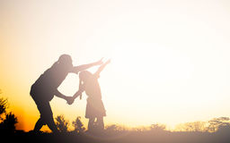 Silhouette of happy family mother and child playing Stock Images