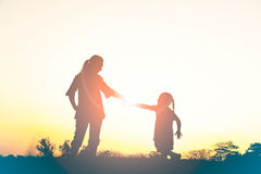 Silhouette of happy family mother and child playing outdoors Stock Photo