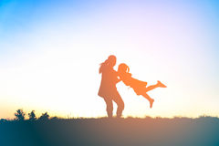 Silhouette of happy family mother and child playing outdoors Royalty Free Stock Photo