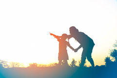 Silhouette of happy family mother and child playing outdoors Stock Image