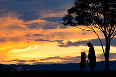 A silhouette of a happy family, mother,girl and infant (women pregnancy) with tree on blurred sunset sky on mountain Royalty Free Stock Photos