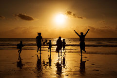 Silhouette of happy family and people running on beach.  Stock Images
