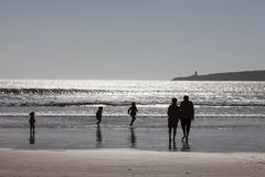 Silhouette of happy family playing on beach. Together at sunset in Essaouira, Morocco stock images