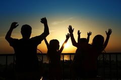 Silhouette of a happy family at sea Stock Photos