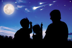 Silhouette of happy family sitting and looking sky at comets. Royalty Free Stock Photos