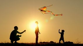 Silhouette of a happy family at sunset. Father and two sons fly a kite in the background of bright sun. Rest and play in
