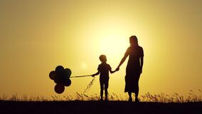 Silhouette of a happy family at sunset. A mother and a child with balloons hold each other`s hands.