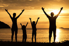 Silhouette of happy family who playing on the beach at the suns. Et time. Concept of friendly family stock photo