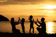 Silhouette of happy family who playing on the beach at the sunse Royalty Free Stock Photography