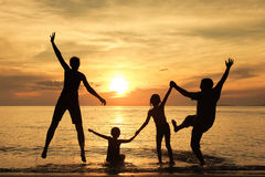 Silhouette of happy family who playing on the beach at the sunset time. Concept of friendly family stock image