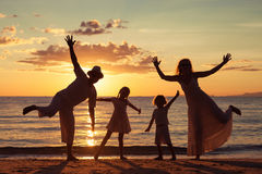 Silhouette of happy family who playing on the beach at the sunse Stock Image