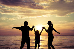 Silhouette of happy family who playing on the beach at the sunset time. Concept of friendly family royalty free stock images