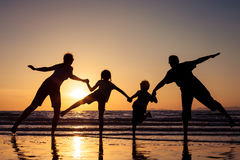 Silhouette of happy family who playing on the beach at the sunset time. Concept of friendly family royalty free stock image