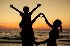 Silhouette of happy family who playing on the beach at the sunse Stock Photography