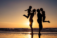 Silhouette of happy family who playing on the beach at the sunset time. Concept of friendly family stock photo