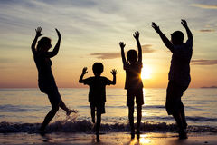 Silhouette of happy family who playing on the beach at the sunset time. People having fun on the beach. Concept of friendly family and of summer vacation royalty free stock photos