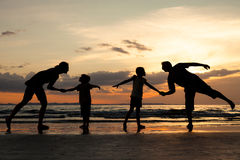 Silhouette of happy family who playing on the beach at the sunset time. People having fun outdoors. Concept of friendly family stock photography