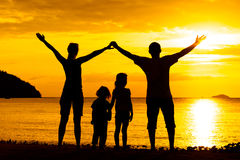 Silhouette of happy family who playing on the beach Stock Images