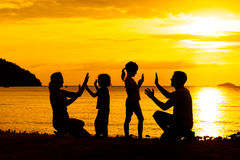 Silhouette of happy family who playing on the beach. At the sunset time stock photo