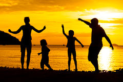 Silhouette of happy family who playing on the beach. At the sunset time stock images