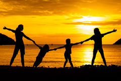 Silhouette of happy family who playing. On the beach at the sunset time stock image