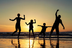 Silhouette of happy family who standing on the beach at the suns Royalty Free Stock Photography