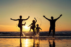 Silhouette of happy family who standing on the beach at the suns Stock Photo