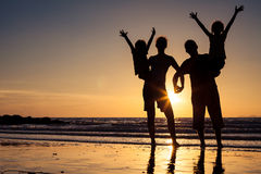 Silhouette of happy family who standing on the beach at the suns Stock Images
